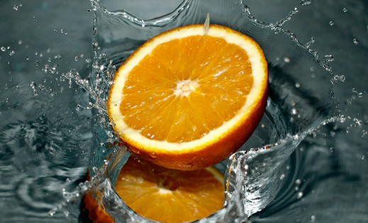 Orange slice splashing in water