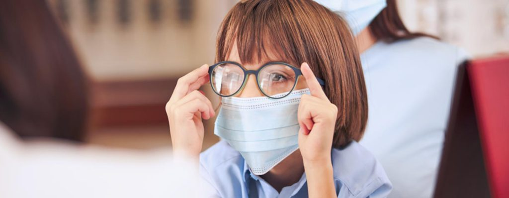 child with mask and glasses looking into the distance