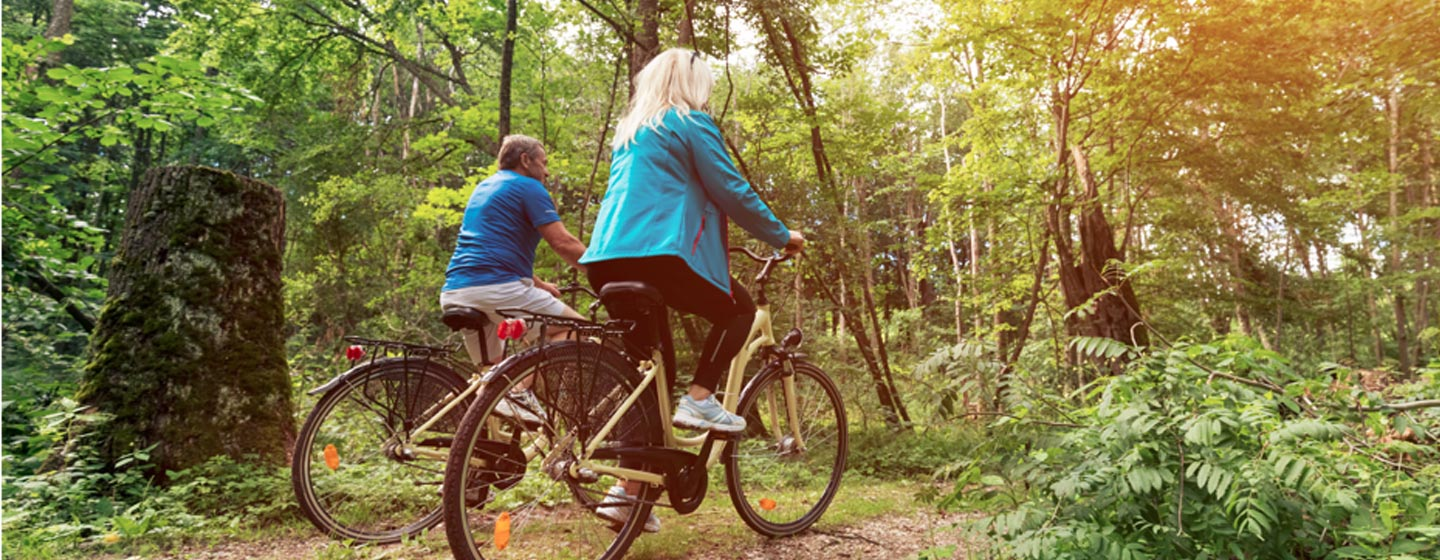 couple cycling through the forest